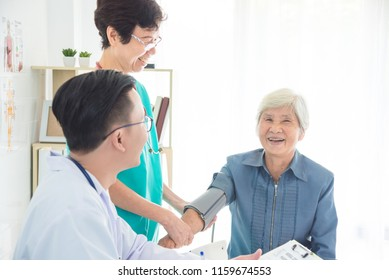 Asian doctor and nurse checking senior woman blood pressure at hospital