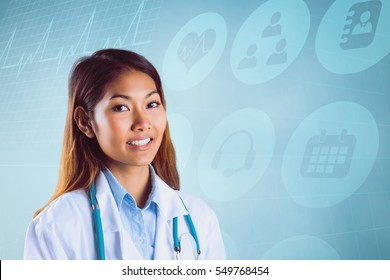 Asian doctor with stethoscope looking at camera against blue background