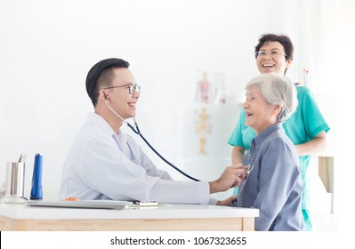 Asian doctor talk with old female patient about disease symptom, elderly health check up , happy hospital