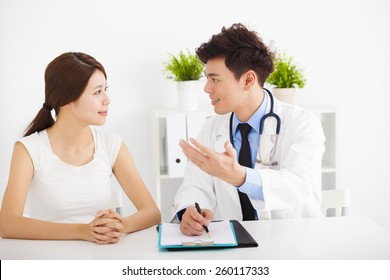 asian doctor talking with female patient in  office