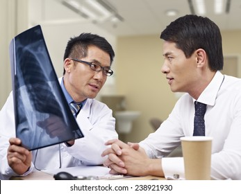 asian doctor talking to patient about x-ray result.