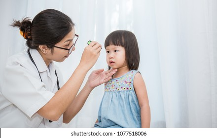 Asian doctor woman examine eyes of little asian girl in the clinic.  Senior looks in instrument for checking eyes at ophthalmologist. Health care and medical for young toddler kid concept.