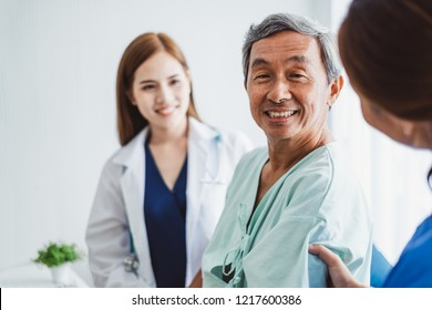 Asian doctor woman and nurse encourage disabled old man patient sitting on wheelchair at hospital, asian medical concept