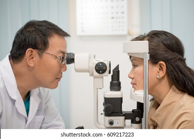 Asian doctor at work during eyesight exam to adult woman in hospital.