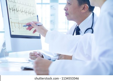 Asian doctors discuss to each other while analysing a patient's health data on computer monitor.