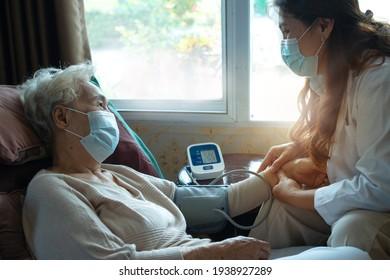 Asian doctors visit elderly patients at home, using blood pressure gauge, doctor and granny wears medical mask, elderly health care concept