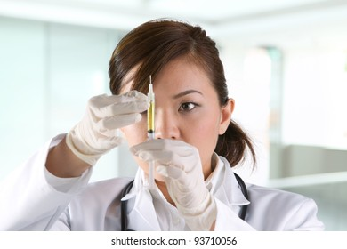 Asian doctor's wearing a green scrubs and stethoscope holding a syringe.