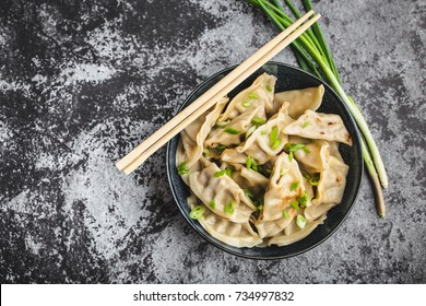 Asian dumplings in bowl, chopsticks, rustic stone background. Top view. Chinese dumplings for dinner. Closeup. Chinese dumplings for dinner/lunch. Traditional Asian/Chinese cuisine. Overhead. Dim sum