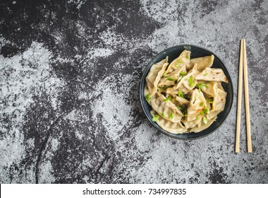 Asian dumplings in bowl, chopsticks, rustic stone background. Top view. Space for text. Chinese dumplings for dinner. Closeup. Copy space. Traditional Asian/Chinese cuisine. Overhead. Dim sum