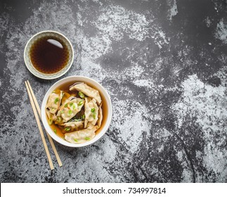 Asian dumplings in broth, bowl, chopsticks, soy sauce, rustic stone background. Top view. Space for text. Chinese dumplings for dinner. Closeup. Traditional Asian/Chinese cuisine. Overhead. Soup