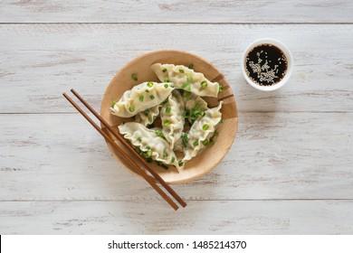 Asian dumplings. Fresh boiled gyoza dumplings with hot steams on wooden plate.