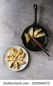 Asian dumplings Gyozas potstickers fried on cast-iron pan and ceramic plate, served with chopsticks over grey texture background. Top view, space.