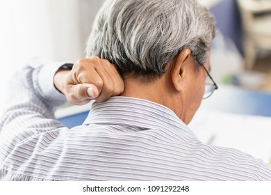 Asian Elder back neck pain using hand to massage and rub.