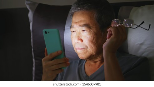 asian elder man has farsighted so he takes off glasses when using smartphone