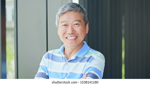 asian elder man look to you with crossed hand and smile