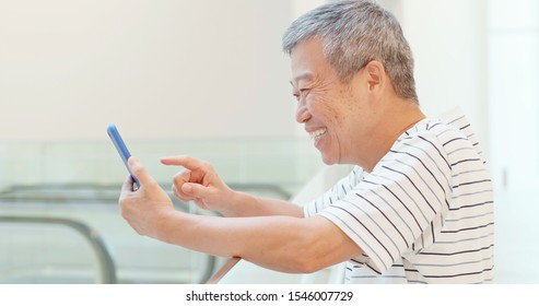 asian elder man watch something on smart phone happily
