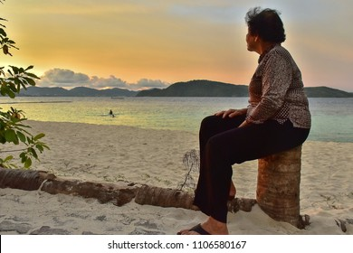 Asian elder woman  does activity alone on the beach on summer season.lonely older woman on sand beach in the evening. with copy space for add text.