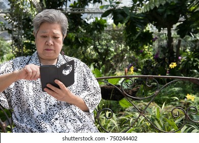asian elder woman holding mobile phone while sitting on bench in garden. elderly female texting message, using app with cellphone in park. senior use smartphone to connect with people on social