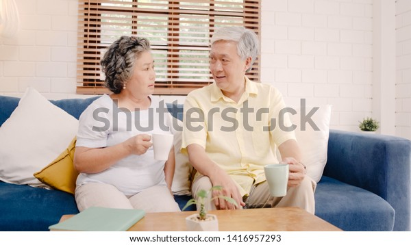 Asian elderly couple drinking warm coffee and talking together in living room at home, couple enjoy love moment while lying on sofa when relaxed at home. Lifestyle senior family at home concept.
