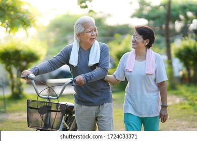 Asian elderly couple holding the bicycle and walking in the park together