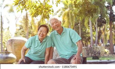 Asian elderly couple laugh together in green natural park background