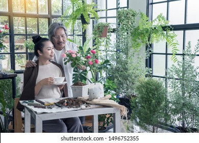 Asian elderly couple sitting drinking coffee and joyful in greenhouse.Lifestyle and hobby after retirement concept