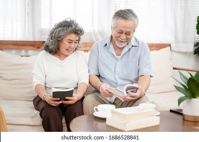 Asian elderly couple was sitting together in the living room reading a book . Health care , life style, pharmacy, medical, elder insurance after retire concept.