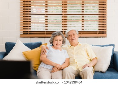 Asian elderly couple watching television in living room at home, sweet couple enjoy love moment while lying on the sofa when relaxed at home. Enjoying time lifestyle senior family at home concept.