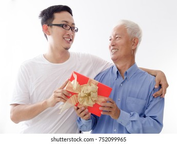 Asian elderly father and son hand holding a gift box and smiling,  standing isolated on white background.