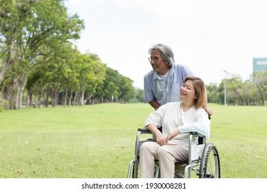 Asiatischer älterer Mann kümmert sich um seine ältere Frau mit verletztem Arm gegossen, während er auf Rollstuhl im Park sitzt. Asiatisches Ehepaar verbringt Zeit zusammen im Freien. Gesundheitswesen