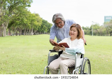 Asian elderly husband taking care his elderly wife with injured arm wrapped in cast while sitting on wheelchair in the park. Asian elderly couple spending time together outdoor. Health care concept