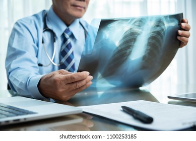 Asian Elderly Male doctor in blue shirt holding and looking to Cancer X-ray film patient at a medical room at hospital. Diagnosis disease about Lung. Covid-19, Coronavirus.