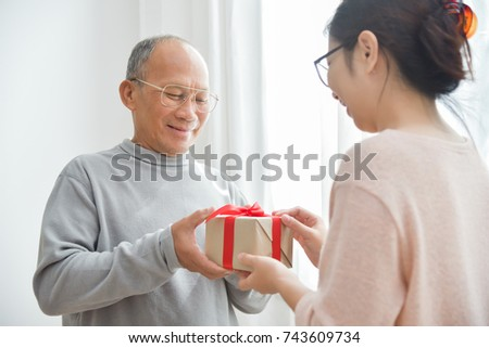 Asian Elderly Man Receiving A Brown Gift Box From Girl For Birthday Christmas And