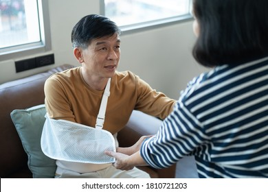 Asian Elderly man wearing arm sling try to stand up while helping by another person. Insurance concept by take care all the time when get illness. Old man get illness after retirement.