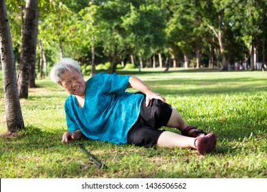 Asian elderly people with walker on floor after falling down in outdoor park,sick senior woman fell to the floor because of dizziness,faint or accident,suffering from illness,leg,knee pain, bone pain