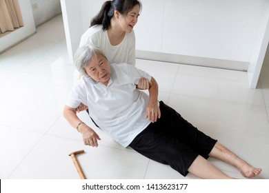 Asian elderly people with walking stick on floor after falling down, caring young woman assistant,sick senior woman fell to the floor because of dizziness,faint,suffering from illness,daughter to help