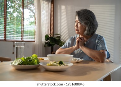 Asian Elderly retired grandmother stay at home with painful face sitting alone on eating table in house. Depressed mature Senior old woman upset feeling unhappy, lonely and missing her family at home.
