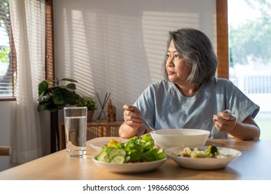 Asian Elderly retired grandmother stay at home with painful face sitting alone on eating table in house. Depressed mature Senior old woman upset feeling unhappy, lonely and missing his family at home