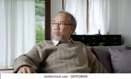 Asian elderly senior male or depressed grandpa at nursing home living room on quarantine looking out window feeling sad missing unhappy thoughtful in mental health care in older people.