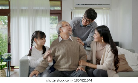 Asian elderly senior male grandpa sitting at sofa couch at home living room on quarantine in concept healthcare, chronic health issue or low back pain in retired older people with family.