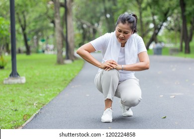 Asian elderly or senior woman accident falling down on floor in the park while running exercise have pain knee ache.