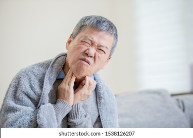 asian elderly sick man has sore throat and feel very uncomfortable at home