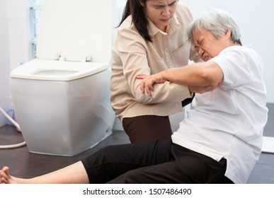 Asian elderly woman on floor in bathroom after falling down because slippery surfaces,caregiver or daughter help,care support to her,sick senior mother fell to the floor in toilet because of dizziness