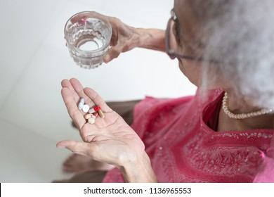 Asian elderly woman are taking and eating medicines and vitamins for help sick and healthy at home,health care concept