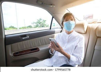 Asian elderly woman wear face mask in car or taxi prevent from covid-19 pandemic illness crisis. New normal and social distancing concept