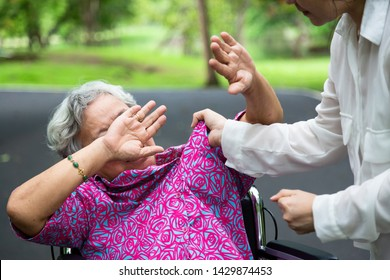Asian elderly woman were physically abused ,attacking in outdoor park,angry young woman raised punishment fist,stop physical abuse senior people,caregiver,family stop violence and aggression concept