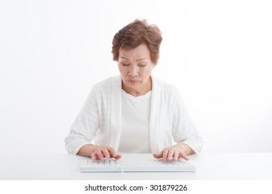Asian elderly women who operates a computer keyboard