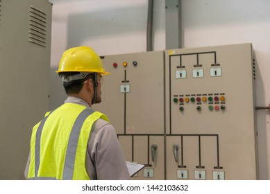 Asian electric engineer holding clipboard for checking and monitoring the electrical system in the control room,Technician thailand people working