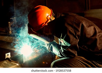 Asian electric welder is welding iron, jetting sparks