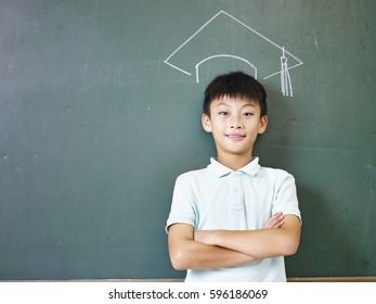 asian elementary school boy standing under a doctoral hat drawn with chalk on blackboard.